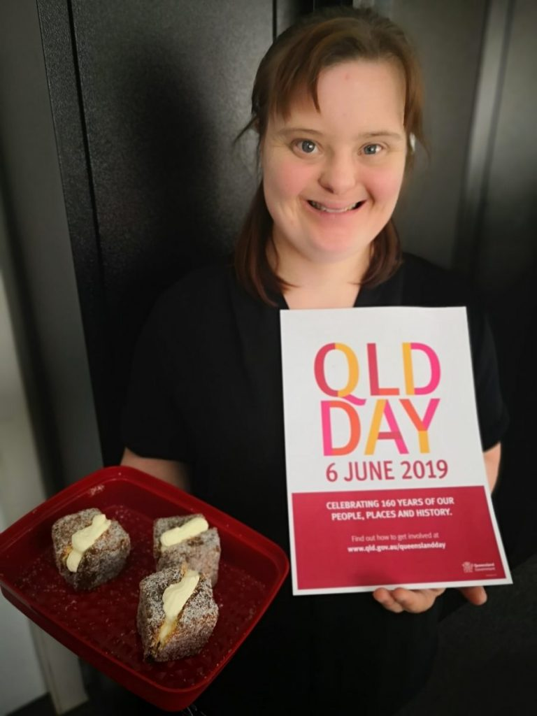 Sophie holding a plate of lamingtons and a flyer promoting Queensland Day.