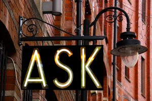 a hanging sign spells ASK in lights