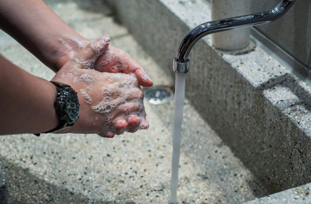 person washing their hands under running tap