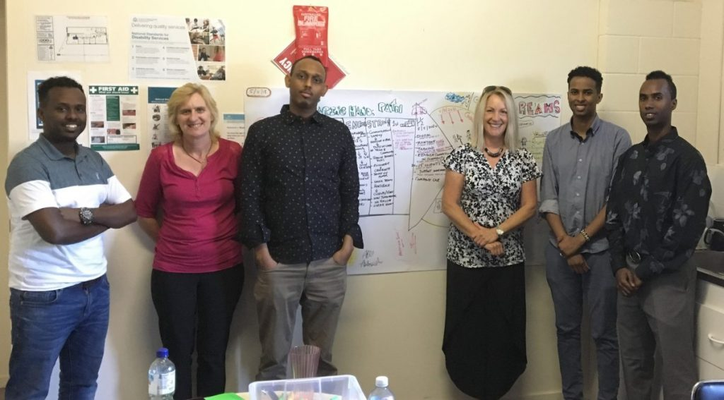 2 women and 4 men stand in front of a cream coloured wall on which a graphical PATH plan is hanging.