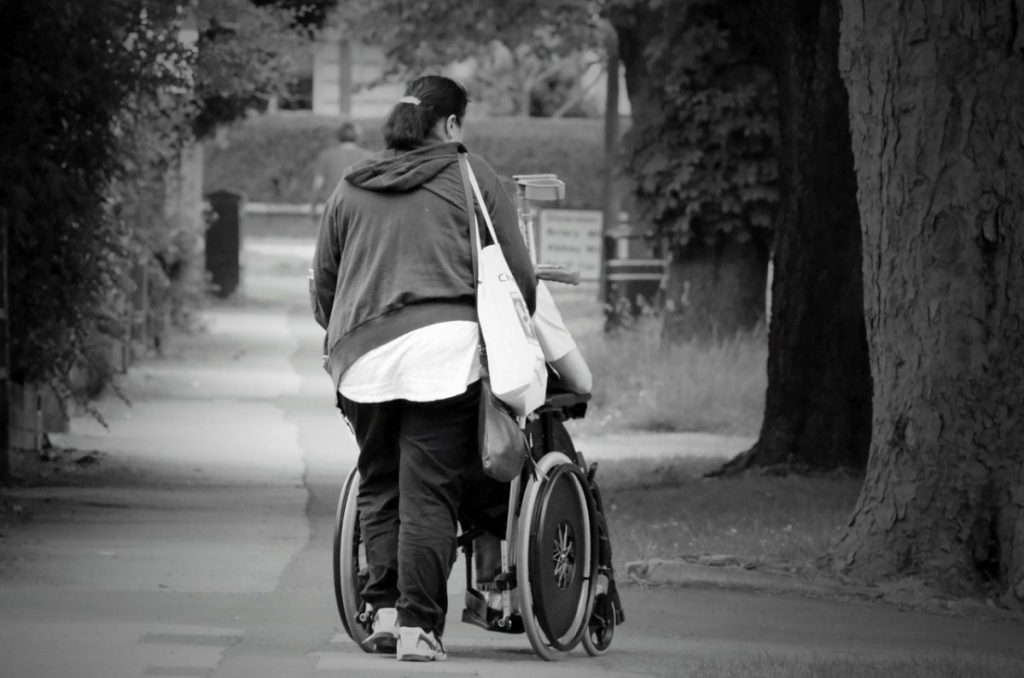 Black and white photo of the back of a woman pushing a person in a wheelchair.